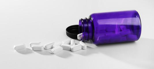 Pills in bottle on white table