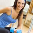 Young woman with dumbbell at home