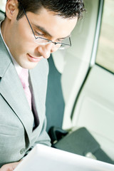 Businessman working with laptop in the car