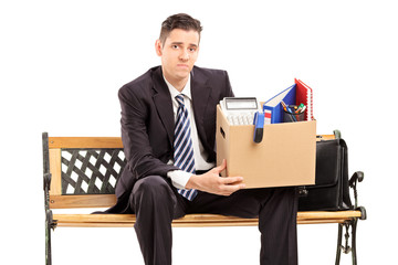 Fired businessman holding a box with his stuff