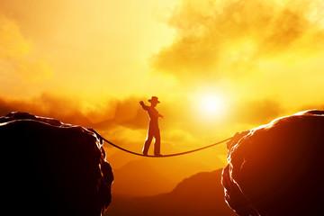 Man walking, balancing on rope over mountains at sunset