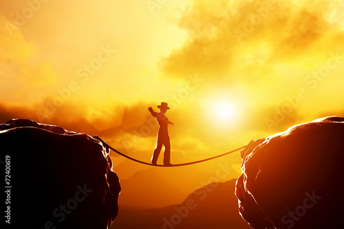 Man walking, balancing on rope over mountains at sunset