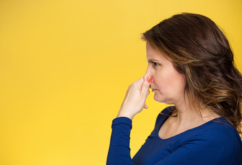 Bad smell woman covers pinches her nose yellow background