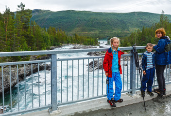 Family near mountain river waterfalls (Norge)