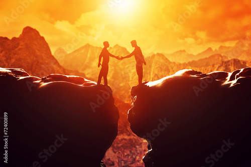 Two men shake hands over precipice. Business - 72400899