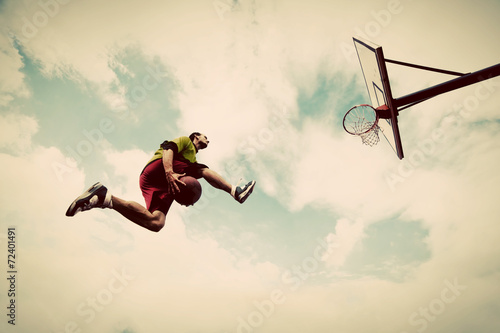Zdjęcia Young man making slam dunk playing streetball, basketball