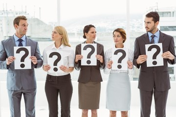 Business people holding question mark signs