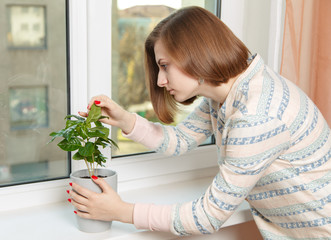 young girl sadly examines houseplant at home