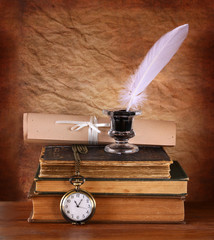 low key image of white Feather, inkwell and ancient books on old