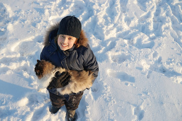 boy plays with a cat  in winter