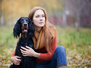 girl and her dog gordon setter in the autumn park