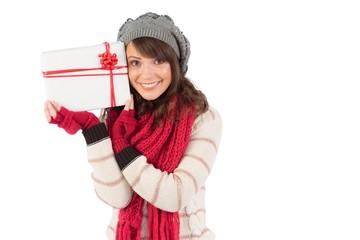 Festive brunette holding white and red gift