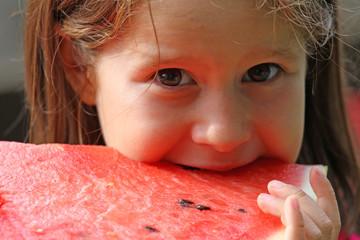 girl brunette eats a huge slice of red watermelon