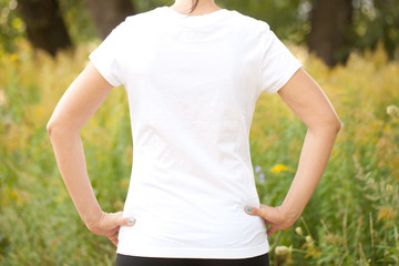 Young woman in white t-shirt outdoors.