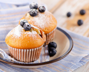 Muffins with  blueberries on a  wooden table