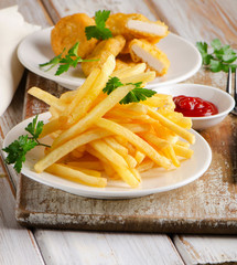 French fries and chicken nuggets on  a wooden table