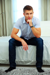 Handsome man in casual cloth sitting on the bed at home