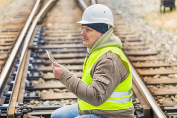 Railway engineer on rails with tablet PC