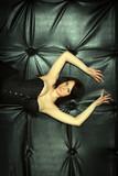Fashion sexy woman lying on the black leather sofa
