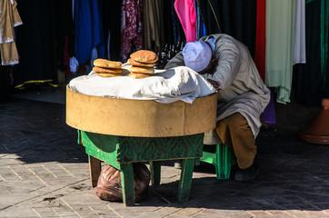 Schlafender Verkäufer von Fladenbrot in Marrakesch