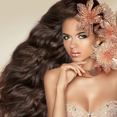 Long wavy hair. Beautiful Attractive brunette Girl With Flowers.