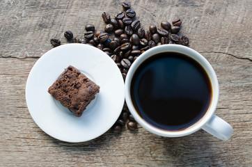 Black coffee with chocolate brownie on grained wood