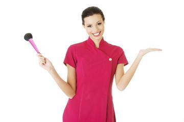 Visage artist holding brushes