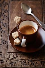 Cup of espresso with brown sugar cubes