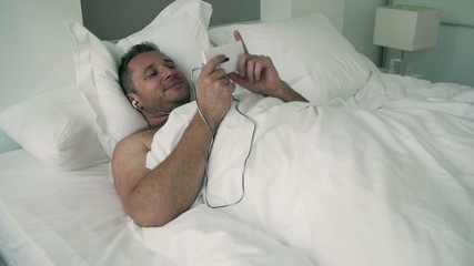 Man lying in bed and watching something on cellphone