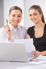 two young business woman or office workers discussing paperwork.