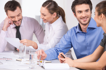Group of young business people talking in couples.