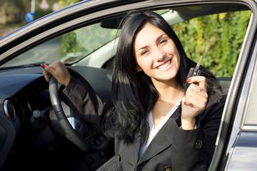 Happy smiling woman inside car showing keys