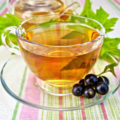 Tea with blackcurrants in cup on tablecloth