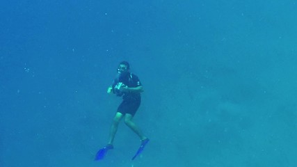 Swimmer taking photo, man swimming with underwater camera