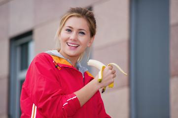 Junge Sportlerin isst eine Banane