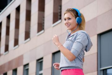 Junge Joggerin hört Musik mit Kopfhörer