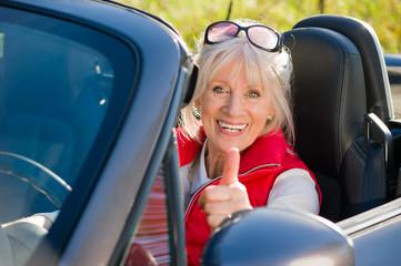 Seniorin im Cabriolet mit Daumen nach oben