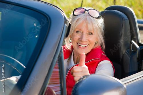 Leinwandbild Motiv Seniorin im Cabriolet mit Daumen nach oben