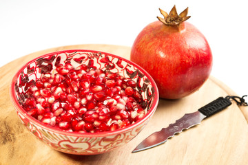 pomegranate seeds in a red bowl