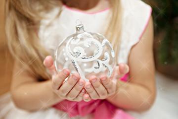 Ребенок с новогодней игрушкой в руках