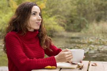 Young attractive woman outside with warm drink and a book
