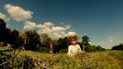 little girl weaves a wreath of grass on the field near the river