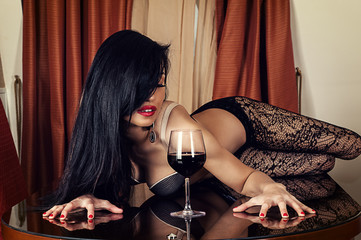 beautiful sexy woman lying on a table with a wine glass