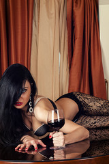 sexy woman lying on a table with a wine glass