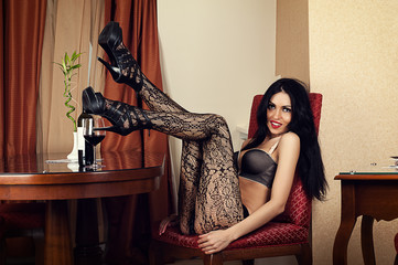 beautiful luxurious woman sitting in a chair in lingerie