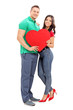 Young couple holding a red heart