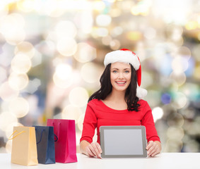 smiling woman with shopping bags and tablet pc