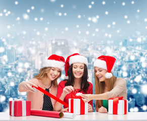 smiling women in santa helper hats packing gifts