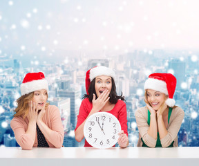 smiling women in santa helper hats with clock