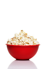 Red bowl with popcorn isolated on white